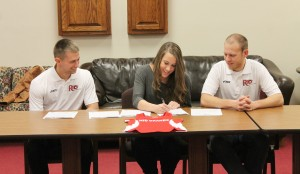 Oak Hill High School's Heidi Hemming signs to continue her track & field career at the University of Rio Grande as Rio assistant coaches Steve Gruenberg (left) and Nick Wilson (right) look on.