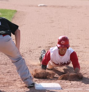 Rio Grande's Grant Tamane brings up a cloud of dirt while diving back into first base during Tuesday's game at Bob Evans Field. Tamane had a hit and scored three runs in the RedStorm's 12-3 win over the Harriers.